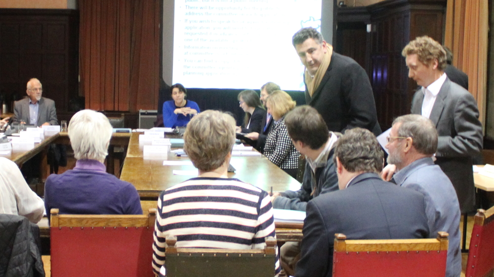 <p>February 2015 West Area Planning Committee. Developer Johnny Sandelson (standing, left) talks to JWT trustees</p>